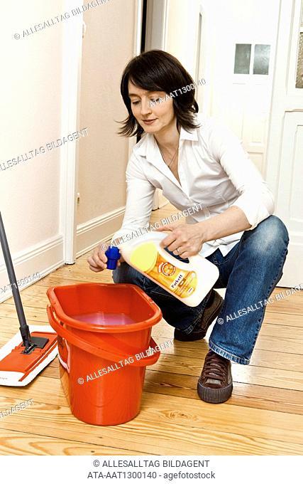 Woman using hardwood floor care product