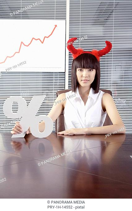 Portrait of a young woman holding percentage sign