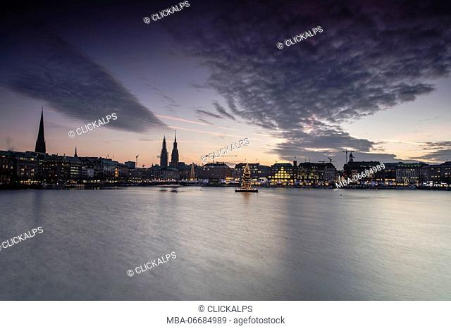 The colors and lights of dusk on Inner Alster Lake with the Christmas Tree suspended in its water Hamburg Germany Europe