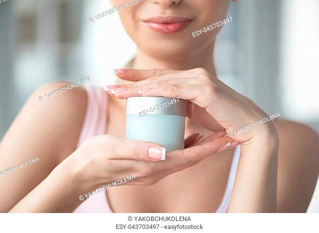 Skin friend. Close up of hands of cheerful young woman holding jar of cream in both palms in front of her body