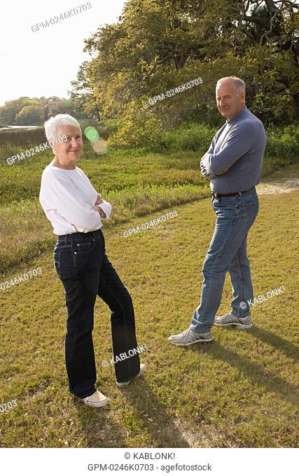 Portrait of senior couple standing in grassland with arms crossed, high angle view