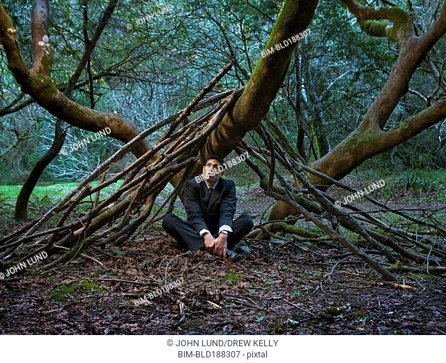 Mixed Race businessman sitting under tree