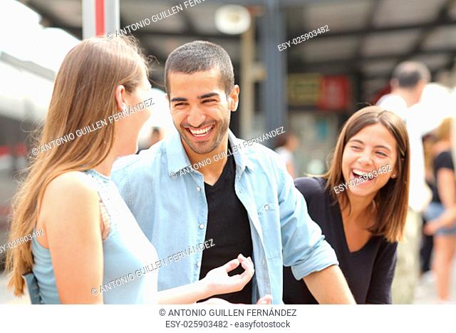 Three friends talking and laughing taking a conversation in a train station