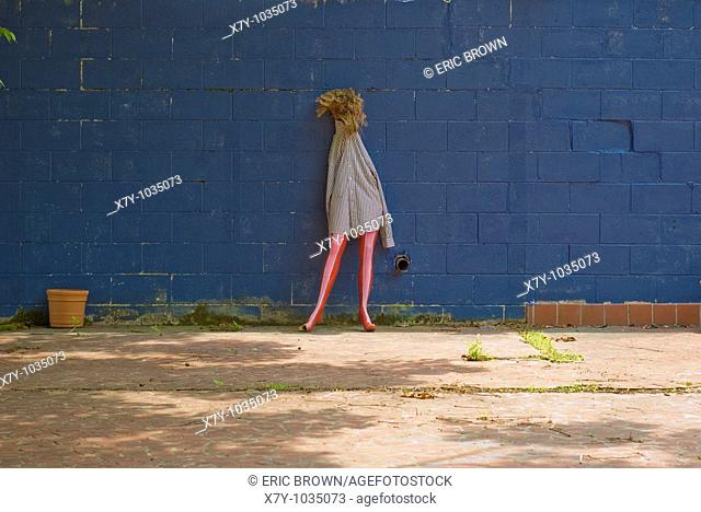 A broom-headed half mannequin with pink painted legs and a striped shirt lean against a blue wall in New Orleans, eight months after Hurrican Katrina