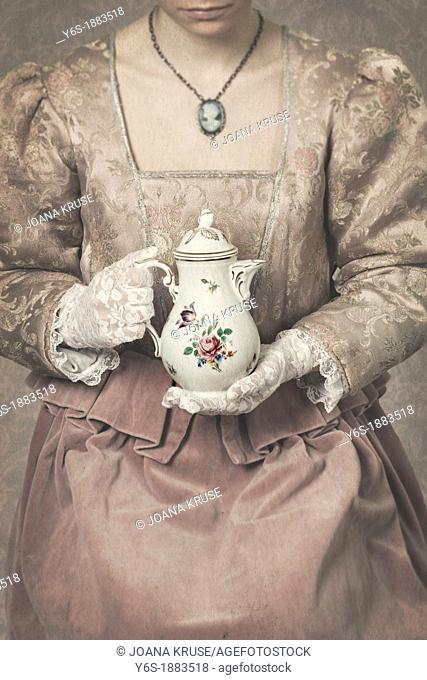 a woman in a period dress is holding a coffee pot