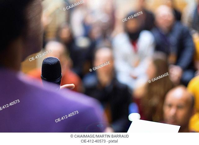 Businessman with microphone speaking to conference audience