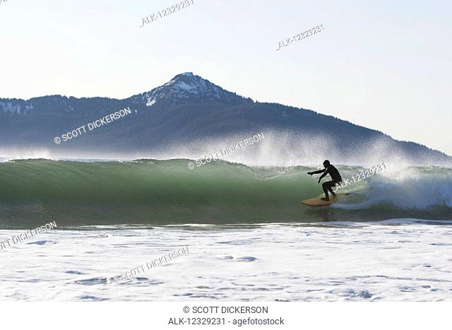 Surfer riding a wave along the Kenai Peninsula Outer Coast, South-central Alaska; Alaska, United States of America
