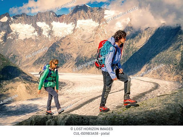 Couple climbing up ridge over Aletsch Glacier, Canton Wallis, Switzerland