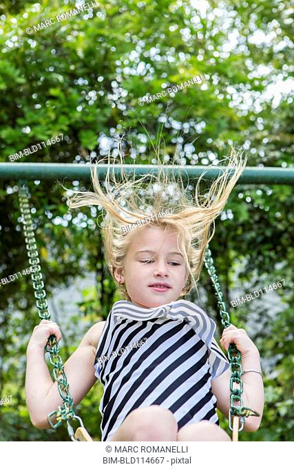 Caucasian girl playing on swing in park