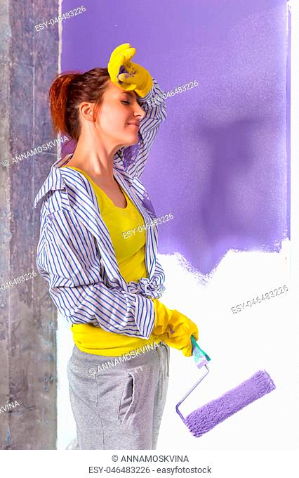 young attractive woman paints white wall and purple paint roller