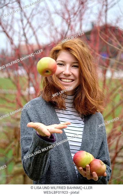 Portrait of redheaded teenage girl with four apples