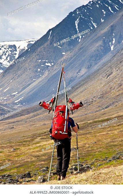 Backpacker carrying skis up Katak Creek valley on the approach to the summit of Mount Chamberlin, Brooks Range, Arctic National Wildlife Refuge