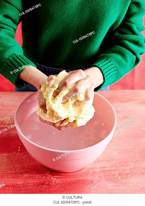 High angle view of mid adult womans mid section bringing togther dough in pink mixing bowl