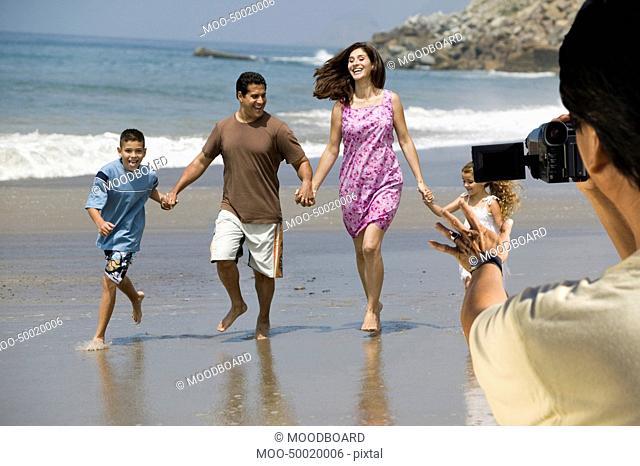Man video recording happy Hispanic Latin family walking at beach