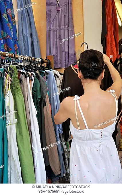 Rear view of a woman looking at dresses on rack, Alcudia old town, Mallorca, Spain, Europe