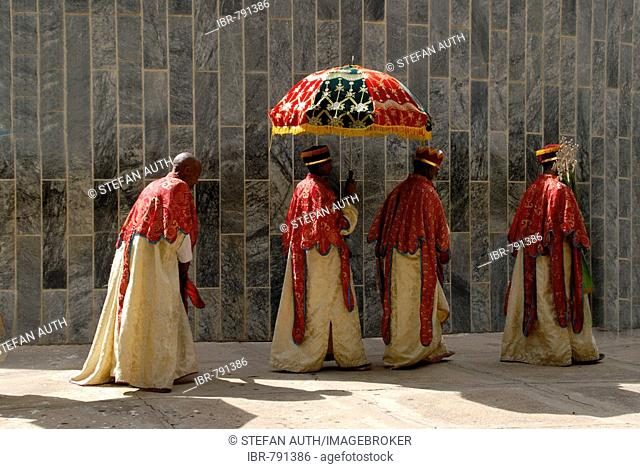 Ethiopian Orthodox procession of priests holding a colourful umbrella walking around the New Cathedral of Axum, Ethiopia, Africa