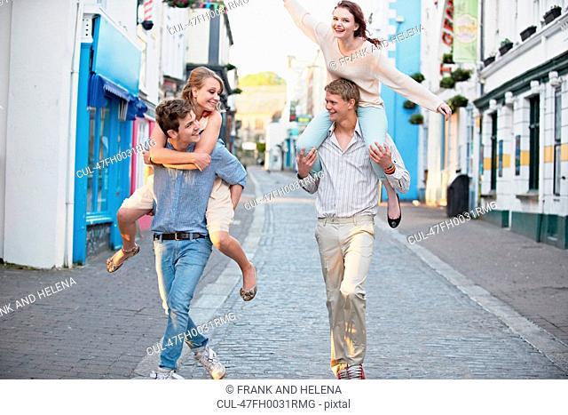 Men carrying girlfriends on city street