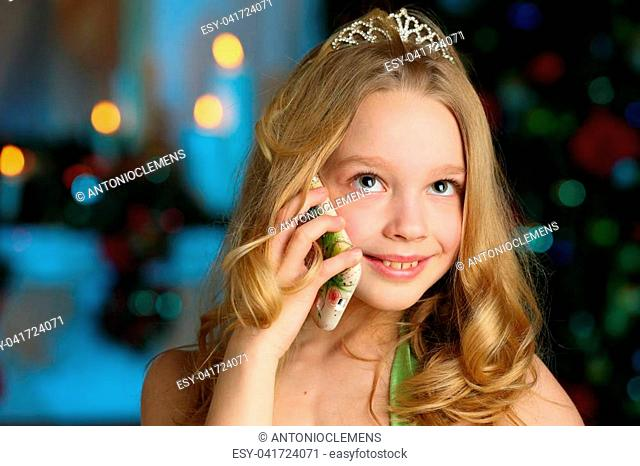 Beautiful charming pretty blond child-girl in a festive green dress on the background of a New Year tree calls elves