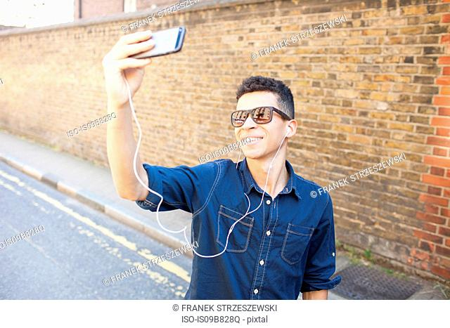 Young man outdoors, taking selfie, using smartphone