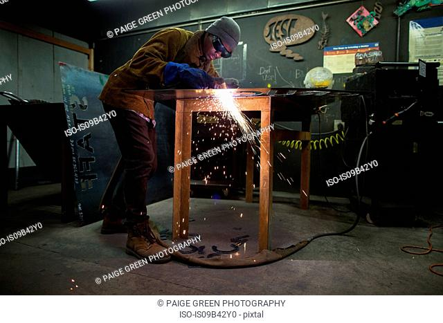 Male metalsmith plasma cutting metal at workbench