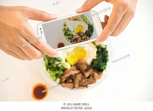Close up of mixed race man photographing food with cell phone