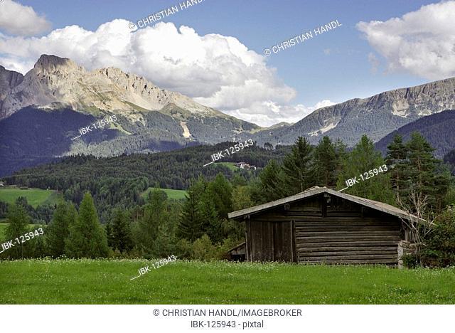 Wooden hut on a meadow behind the mountain range Rosengarten, Deutschnofen, Eggen valley, South Tyrol, Italy