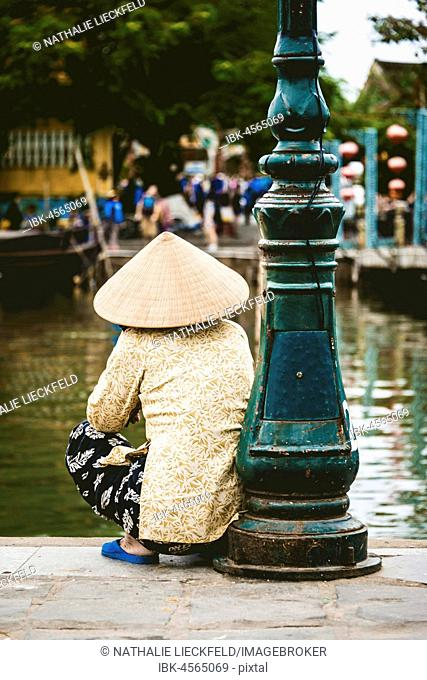 Native woman with straw hat sits on the shore of the Thu Bon River, Hoi An, Vietnam