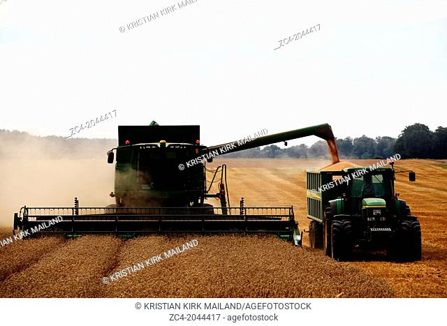 Harvester unloading the harvest to a tractor