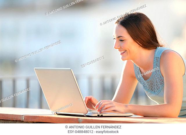 Portrait of a happy girl writing on laptop on a balcony wall
