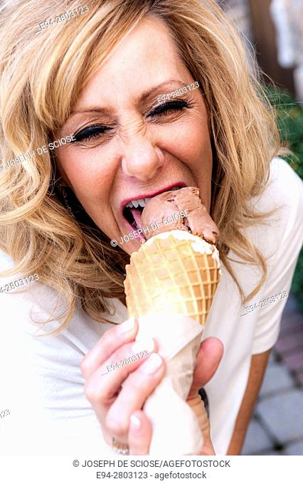 56 year old woman playfully licking an ice cream cone and flirting to the camera
