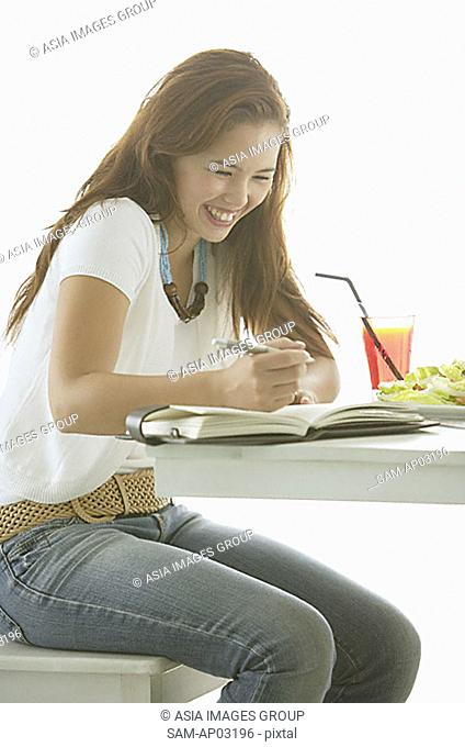 One woman sitting at table, writing in notebook, smiling