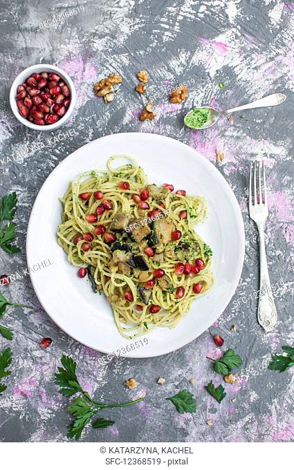 Spaghetti with parsley walnut pesto, eggplant and pomegranate