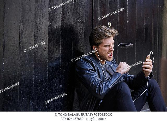 Young man listening music with smartphone earphones sitting in the street black door