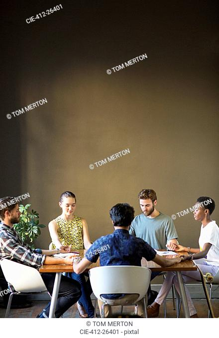 Serene casual business people holding hands with eyes closed at office table