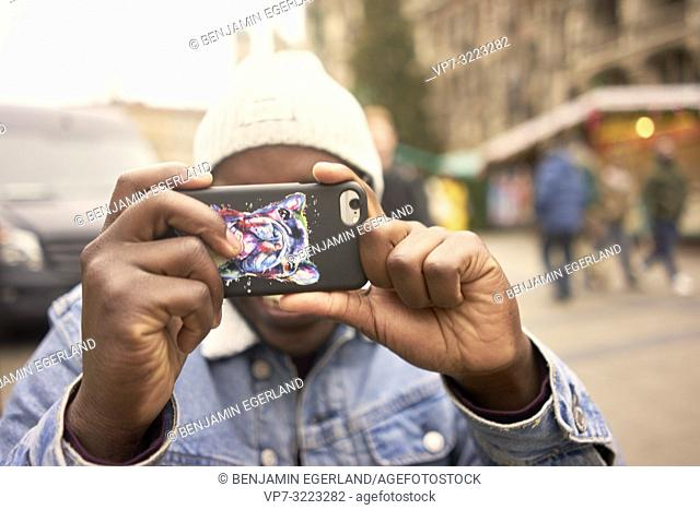young man using smartphone, taking photo, in Munich, Germany