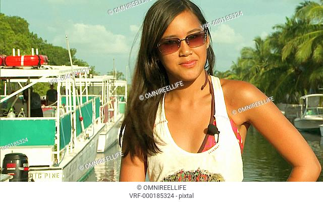 Young smiling female wearing sunglasses facing camera with hand on hip with boats and trees behind