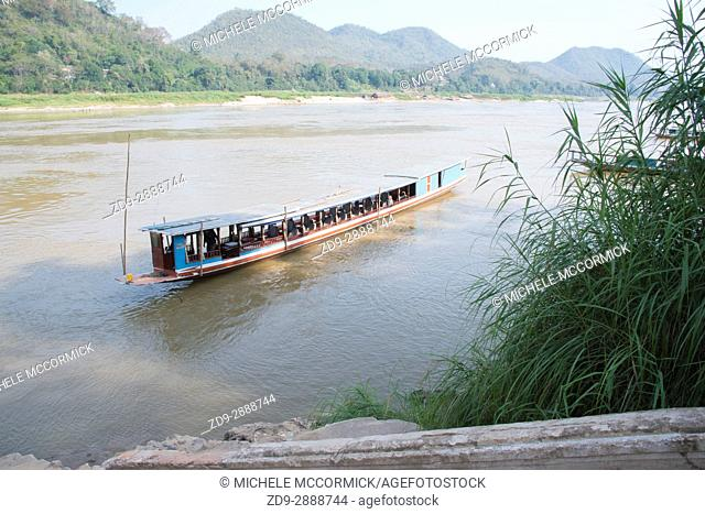 A narrow boat carries tourists up the Mekong River in Laos