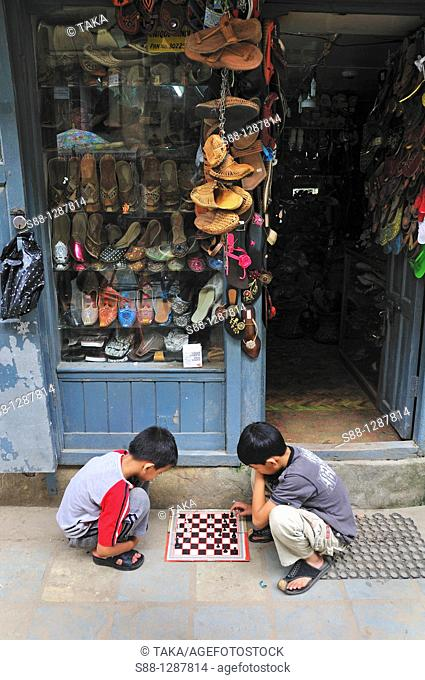 Children playing chess in front of the shop