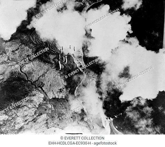World War II, original caption: 'Kiska, Aleutian Islands. Bombs dropping in train from a United States Army Air Force plane on a Jap objective