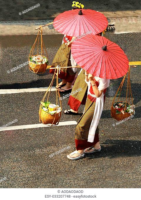 female shopkeeper in Thai old fashioned traditional cloth ,red paper umbrella and load Thai food in bamboo basket walk on road, Thailand
