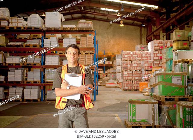 Hispanic worker holding clipboard in warehouse