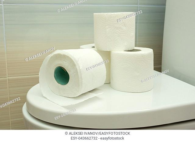 Several rolls of toilet paper are on the toilet lid