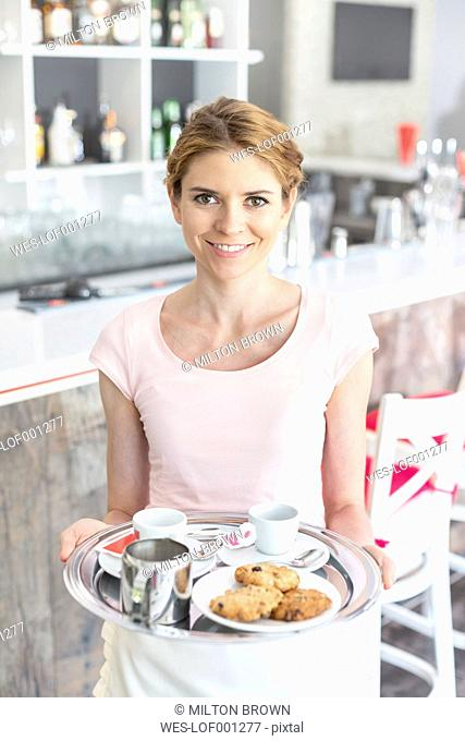 Waitress in a cafe serving pastries and coffee