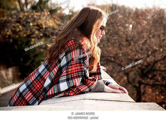 Girl with plaid blanket looking over wall