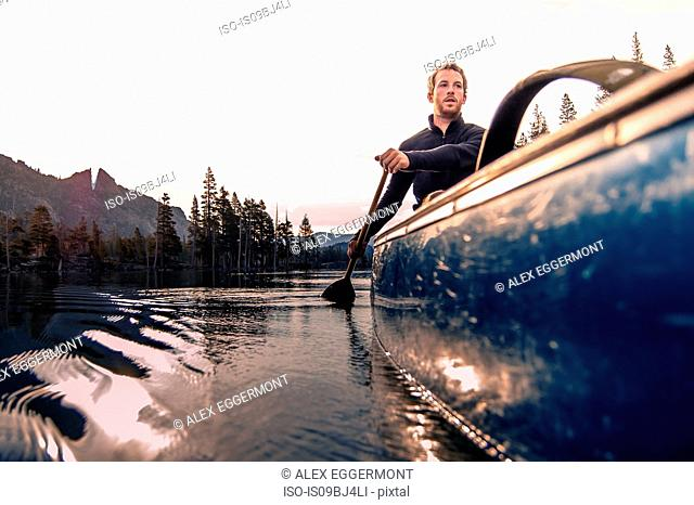 Young man canoeing on Echo Lake, High Sierras, California, USA