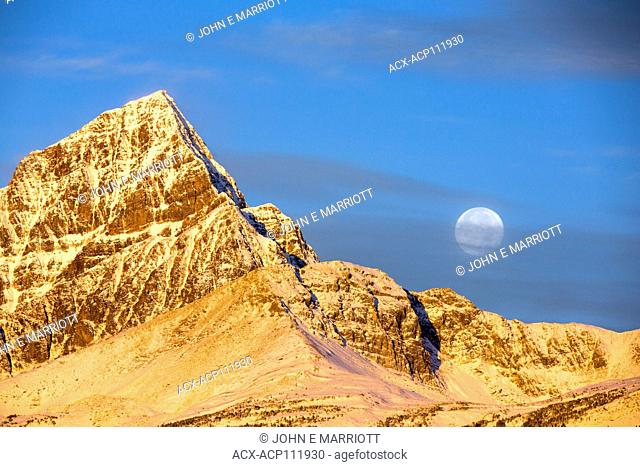 Sunrise and moon set over a sun-washed peak in Jasper National Park, Alberta, Canada