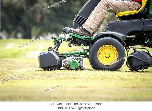 Man using ride lawn mower to cut turf grass