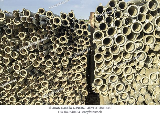 Irrigation metal pipes stacked outdoors out of watering season. Last sunset rays