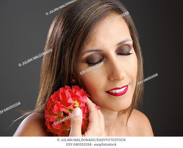 Young woman showing her beauty with a flower