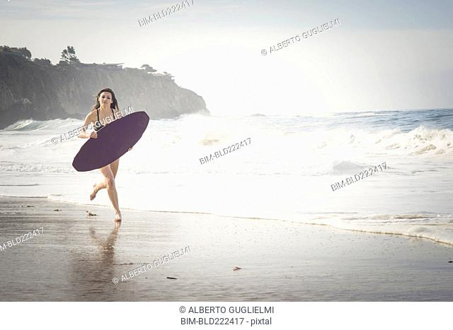Caucasian woman running with skimboard at beach
